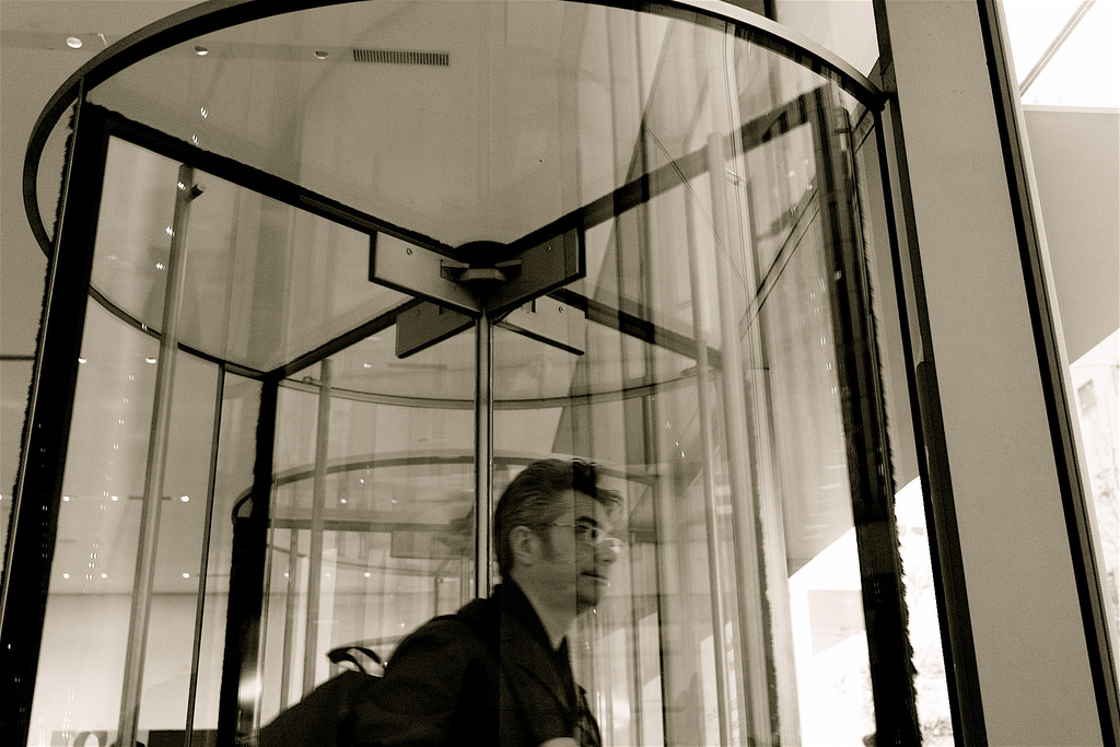 Photo of man exiting building through a revolving glass door at MOMA