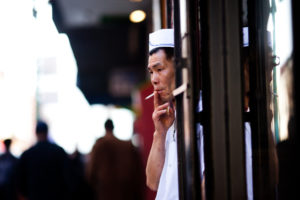 A cook pokes his head out out of a doorway for a smoke break.