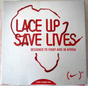 "Ad from the Red Campaign, showing Nike's support for fighting AIDS in Africa. The poster reads, ""Lace Up, Save Lives."""