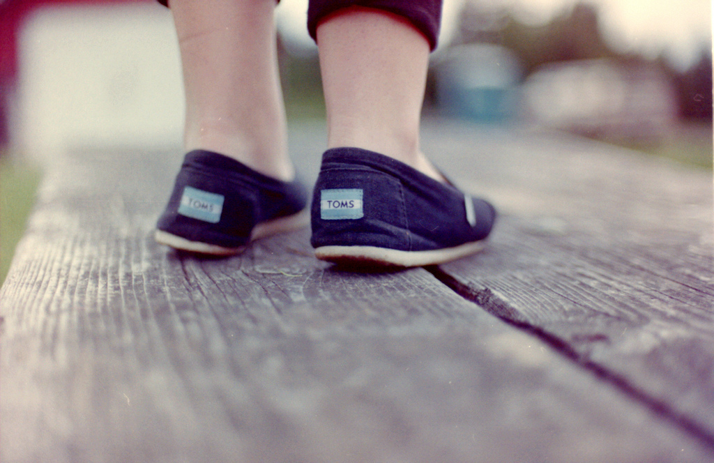 young child wearing a pair of TOMS shoes