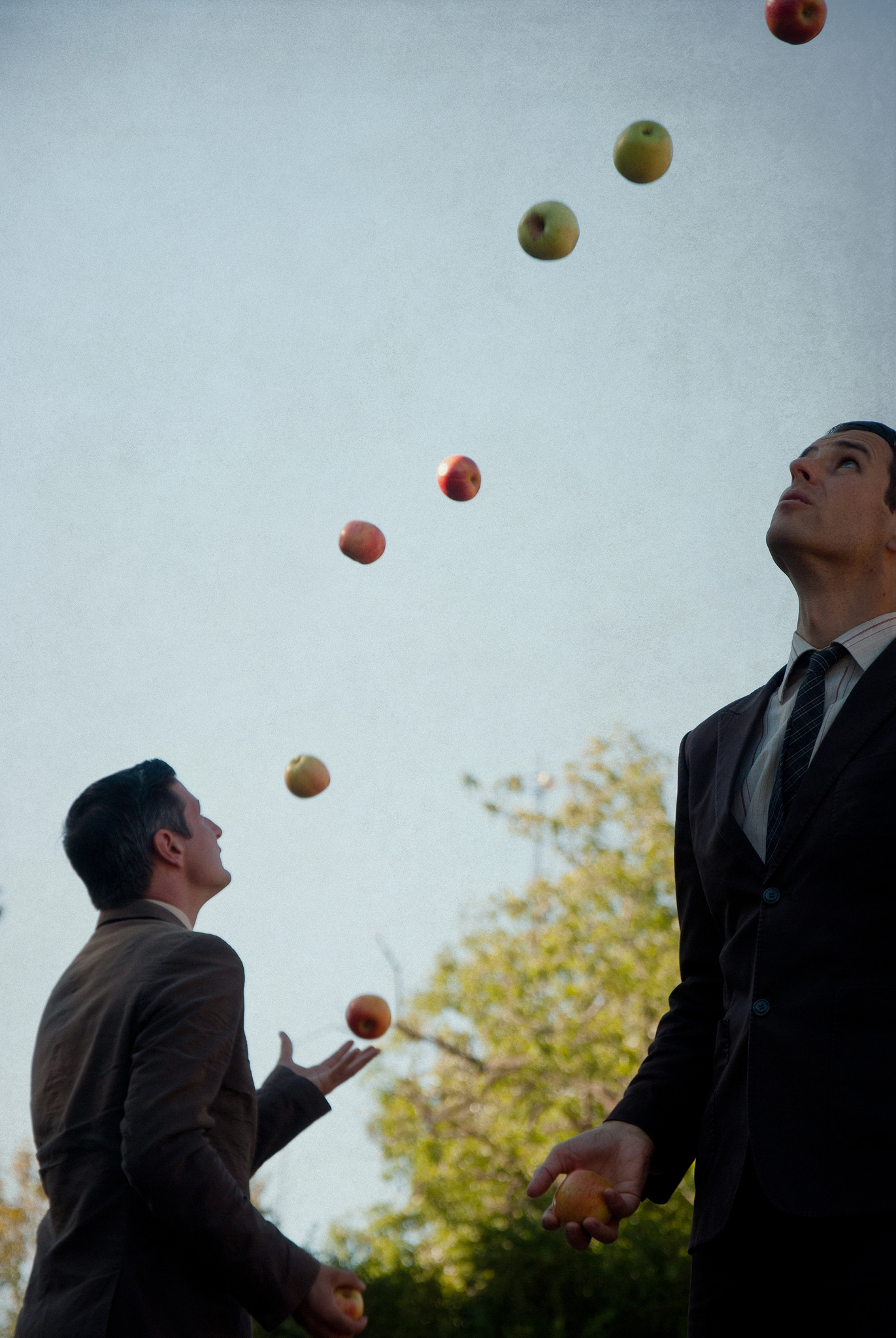Two men wearing suites juggle apples