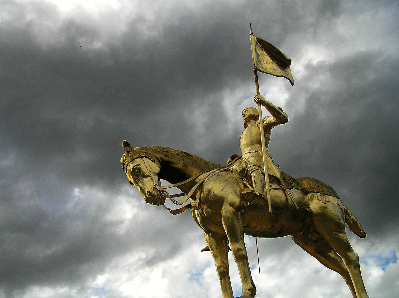Statue of a knight riding a horse; the knight is holding a flag