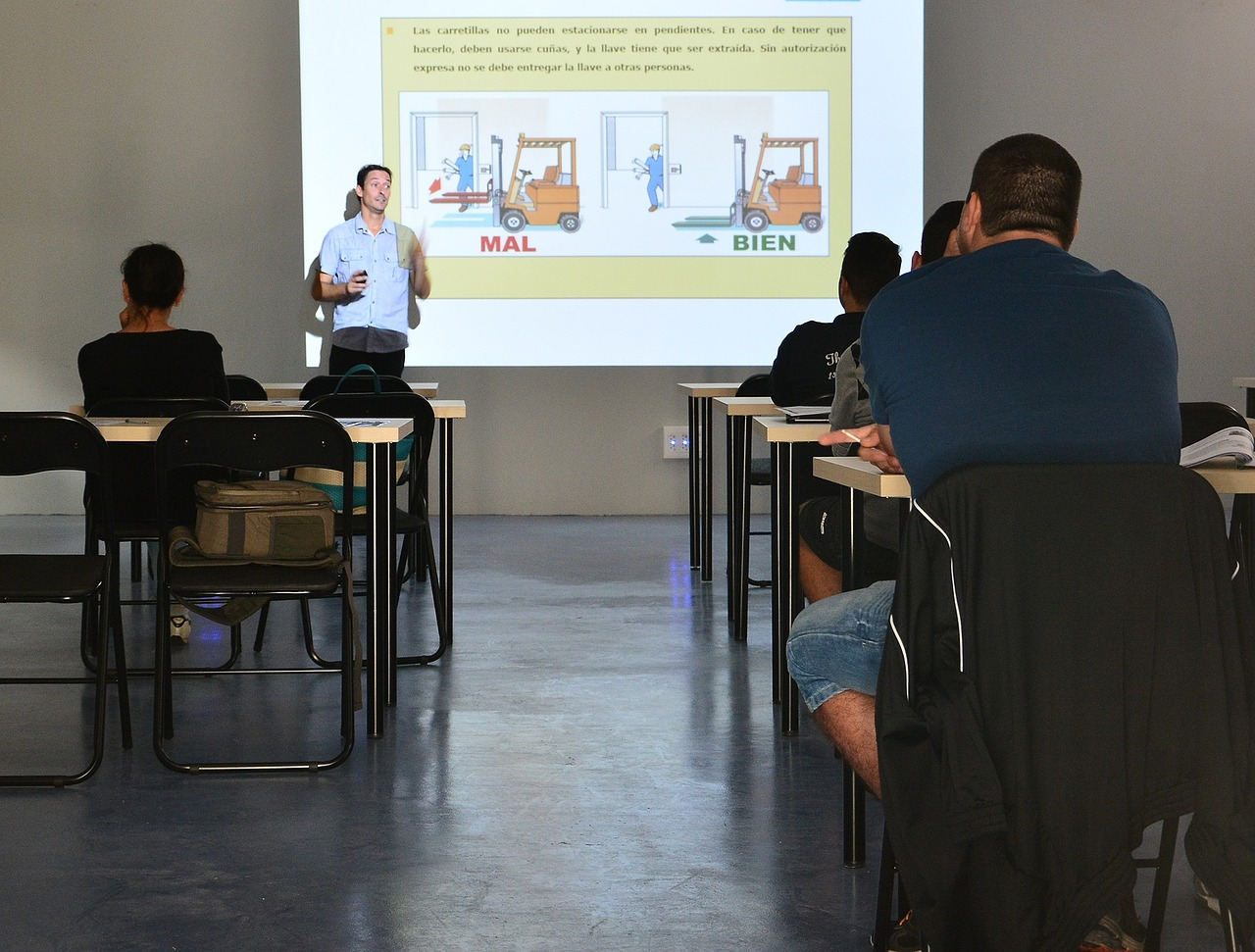 A group of employees listens to a man give a presentation