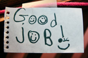 """Sheet of paper that has """"Good job!"""" scrawled on it in a child's handwriting."""