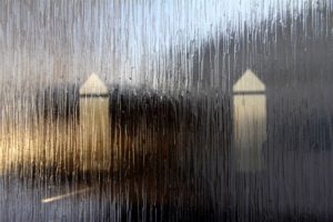 Photo collage showing two pale towers viewed through a rainy window