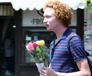 Photo of a worried-looking young guy carrying a small bouquet of roses.