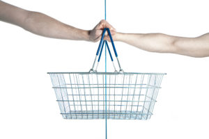 An empty wire shopping basket is shown, held by two different hands on opposite sides.
