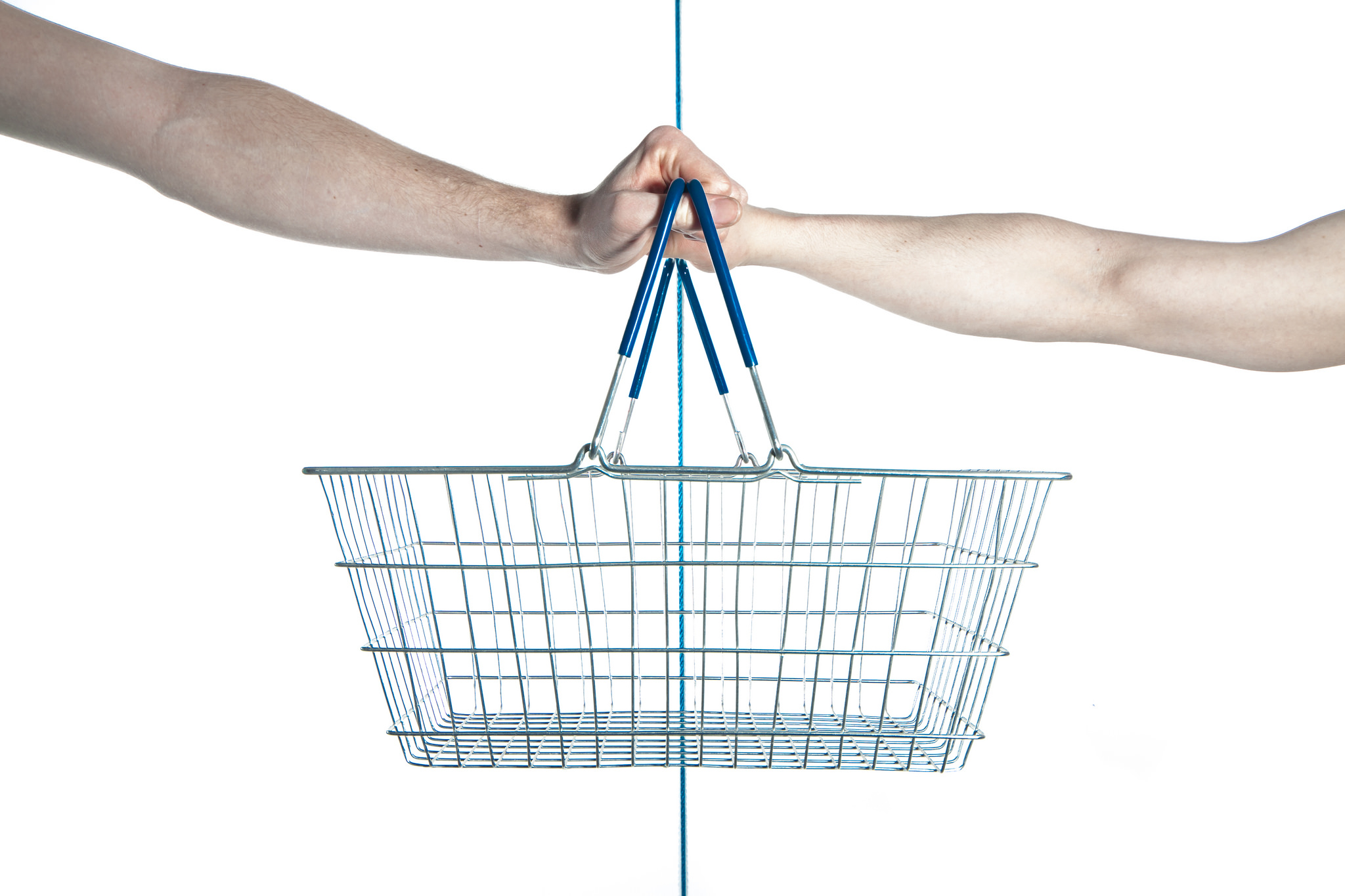 An empty wire shopping basket held by two different hands on opposite sides.