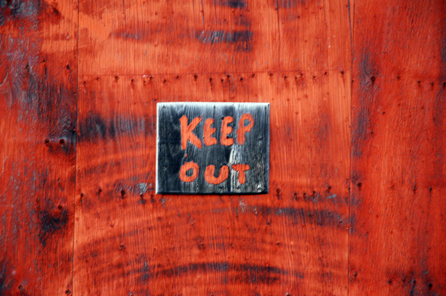 """Small black sign with red lettering that reads, """"Keep Out."""" Background is red, too."""