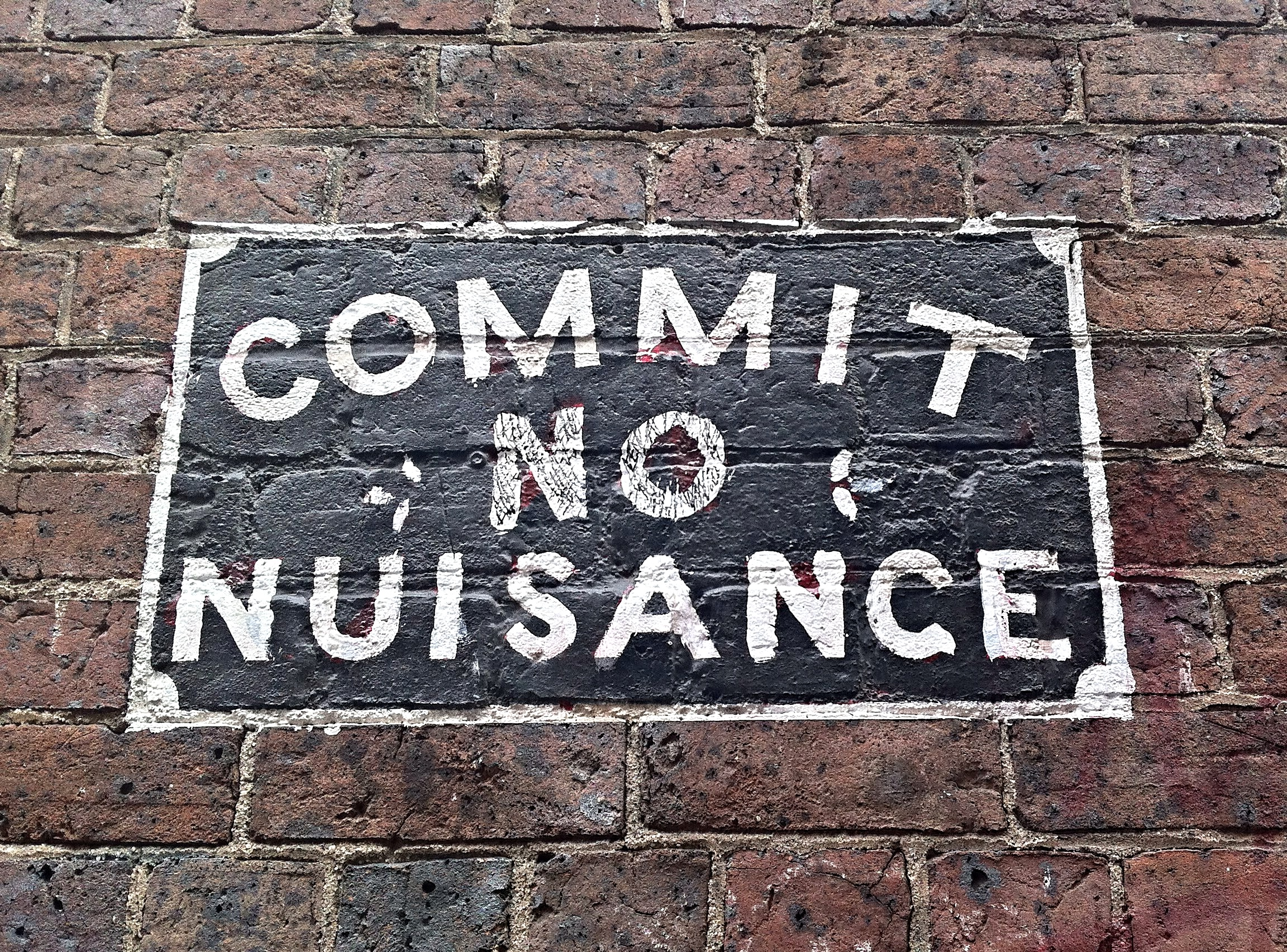 """Sign on a brick wall that says """"Commit No Nuisance."""""""