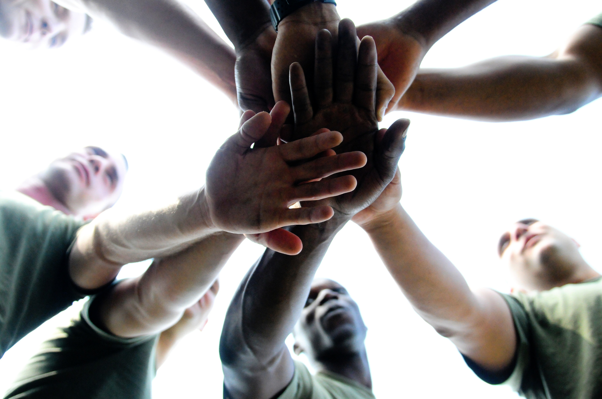 team huddle where each person places a hand in the center atop another member's hand.