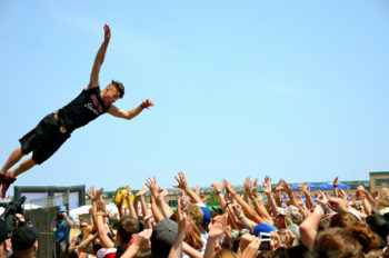 A man is shown diving into a crowd of people with up-stretched hands. Photo title: Trust Dive.