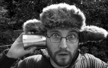 "Humorous photo of a guy in a beaver hat holding a soup-can ""telephone"" to his ear."
