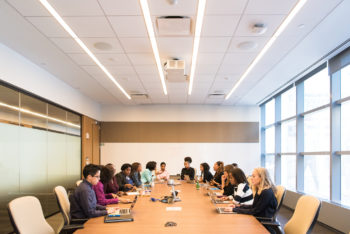A group of people hold a meeting in a conference room.
