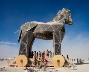 Photo of a large Trojan horse outside. People stand around at the base of the horse.