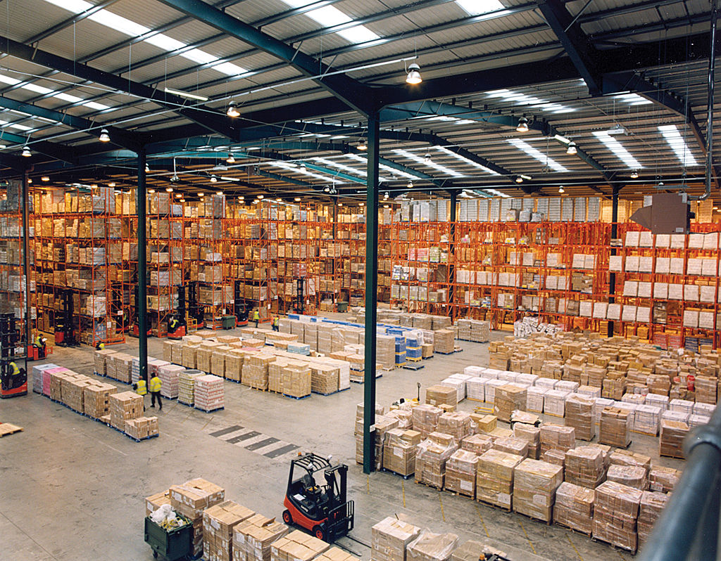 Photo of a giant warehouse with pallets loaded with goods and forklifts.