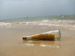 Photo of a glass bottle with a message in it, lying in the sand at the beach.