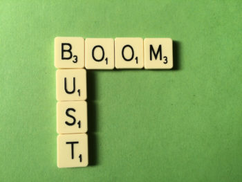 Scrabble tiles spell the words BOOM and BUST; green background