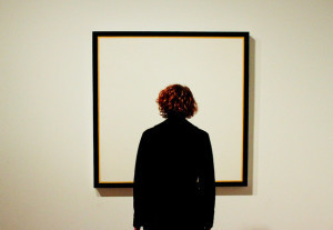 Photo of a woman staring at an empty frame hanging on a wall