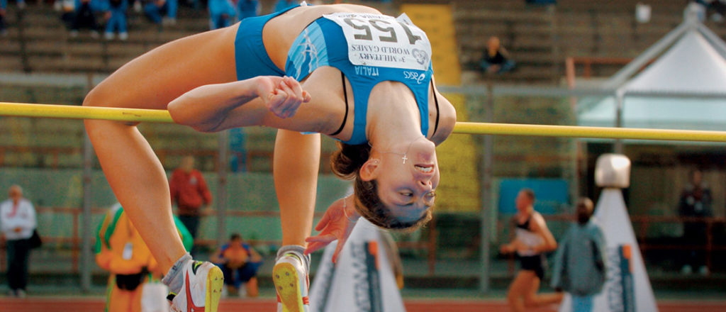 Illustration shows a woman, upside-down with an arched back, going over a pole vault.