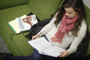 Young woman sitting on a green sofa with a statistics book next to her, reading another book with pencil in hand