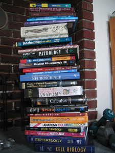 Photo of a stack of roughly 20 textbooks. Prominent titles include Gray's Anatomy, Pathology, Fundamental Neuroscience, and Calculus.