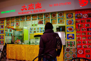 Person with back to camera at counter of Hong Kong Style Wokman's Kitchen. The walls, counter, and menu board are all plastered with menu options.