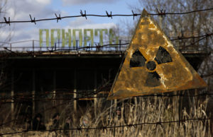 Dirty radioactive sign handing from fence.