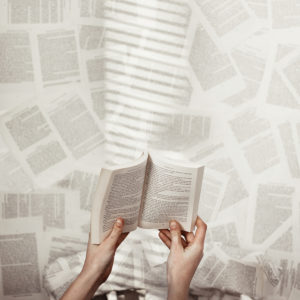 A pair of hands holding an open book against a background of blurred printed pages