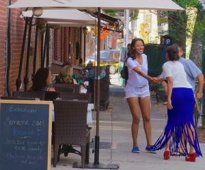 Women shaking hand on a city sidewalk