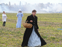 Woman in period dress holding basket