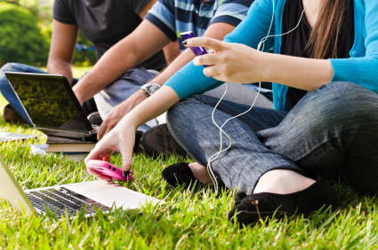 Students sitting outdoors with laptop computers, cell phones, and mp3 players