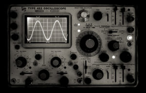 A black and white photo of an oscilloscope displaying a sound wave.