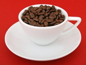 Photo shows a white cup filled with coffee beans on a white saucer.