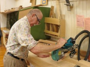 Man using a table saw in a woodshop.