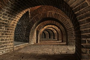 Series of brick archways at the base of a building.