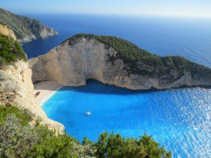 Photo shows blue ocean water in an inlet between rock structures.