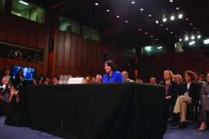 An image of Sonia Sotomayor standing behind a table with a group of people seated behind.