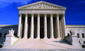 An image of the Supreme Court building. In the foreground, a set of stairs is bracketed by statues on either side, leading up to a portico. The portico has a roof supported by several tall columns.
