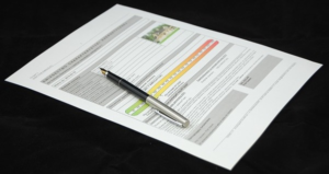 A piece of paper is displayed on a black table. The paper has ineligible text on it and a half black and half silver pen laying on top of it.