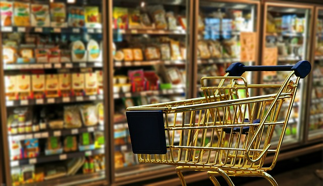 A golden shopping cart is stationary in front of the frozen foods aisle at a grocery store. The shopping cart is empty.