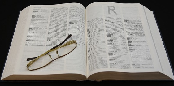 A dictionary has been opened to the page where all words that begin with R is. On the dictionary is a folded pair of reading glasses.