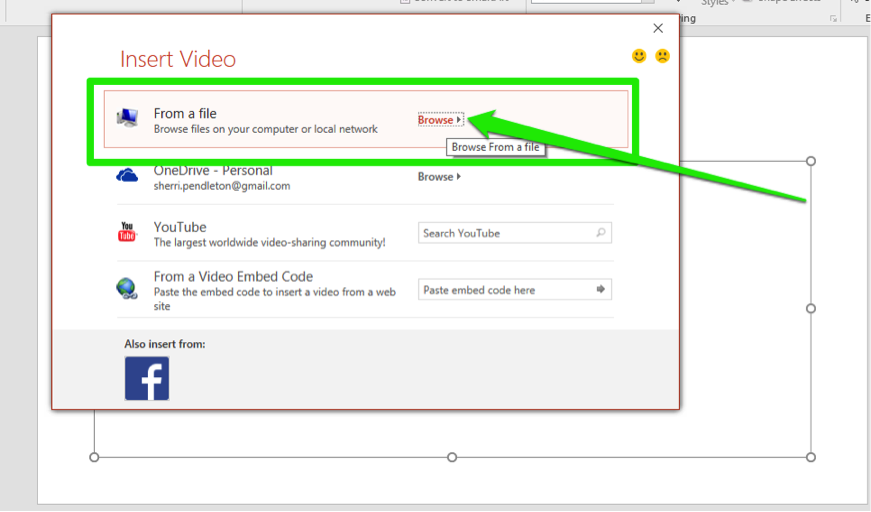 A Microsoft powerpoint is open. An insert video dialog box is open with four options. The first option has been selected which is to choose a video from the computers files. A green arrow points at the browse button.