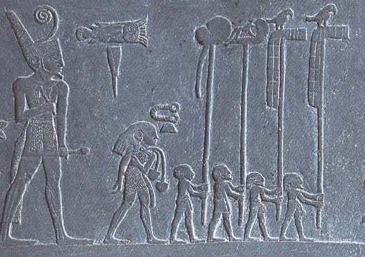 Photograph of stone tablet. It depicts six figures carved into the stone. They appear to be walking in the line. The largest figure is at the end of the line, each figure in front is progressively smaller.