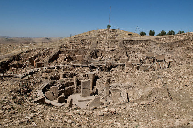 Photograph depicts ruins of Göbekli Tepe. The photo features a mound of dirt and rock with the remains of pillars and slabs that once formed a sacred structure.