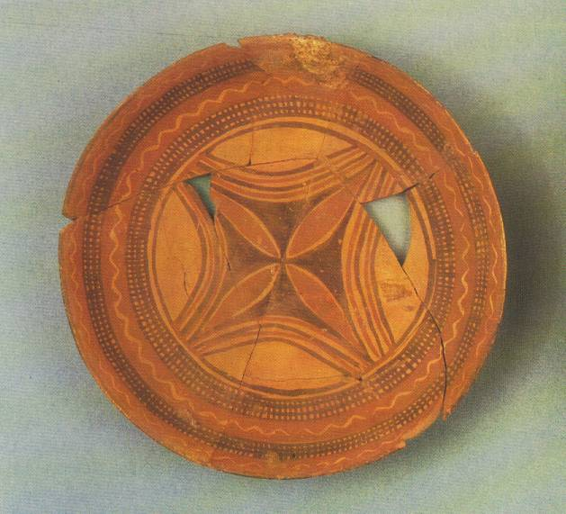 Photo depicts a flat, circular piece of pottery reconstructed from broken shards. Some of the pieces are missing.