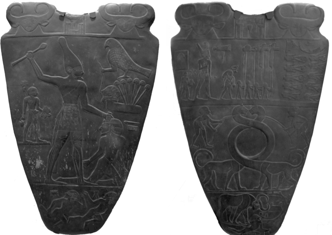Photo that depicts front and back view of Narmer Palette, carved from soft dark gray-green siltstone. The scene on the front features large Narmer wielding a mace wearing a flower crown. On the left of the king is a man bearing the king's sandals. To the right of the king is a kneeling prisoner, who is about to be struck by the king. The scene on the back features a procession with King Narmer at the top. Below the procession, two men are holding ropes tied to the outstretched, intertwining necks of a mythical serpoard (serpent/leopard).