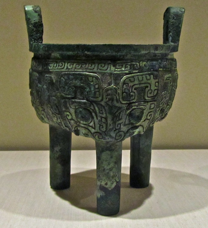 Photograph of a cooking pot that stands upright on three legs. It is covered with intricate carvings.