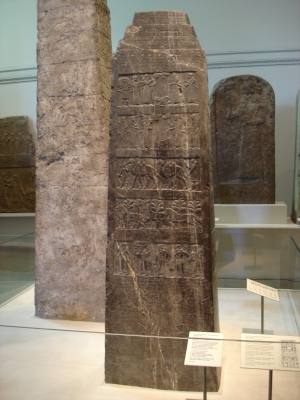 Photo of black limestone Assyrian sculpture with many scenes in bas-relief and inscriptions