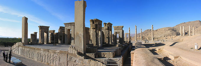Photo depicts the ruins of Persepolis. It shows a raised foundation with steps on either side. On the foundation, there are various structures that look like doorframes.